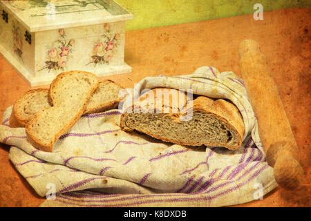 Bread loaf wrapped in kitchen cloth, two bread slices next to it, and rolling pin. Decoupage box is partially visible. - Stock Image