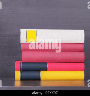 stack of new colorful books in the wooden bookself - Stock Image