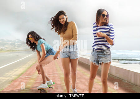 Three girl friends walking and doing roller skating on a promenade - Stock Image