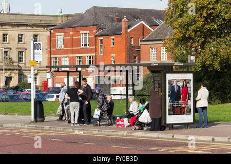 Passengers waiting in the  bus shelter at stop BB on Black Horse Street, Bolton, adjacent to Moor Lane bus station. - Stock Image