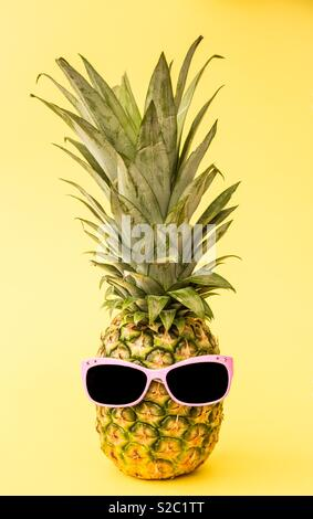 A funny pineapple wearing pink sunglasses on a yellow background - Stock Image