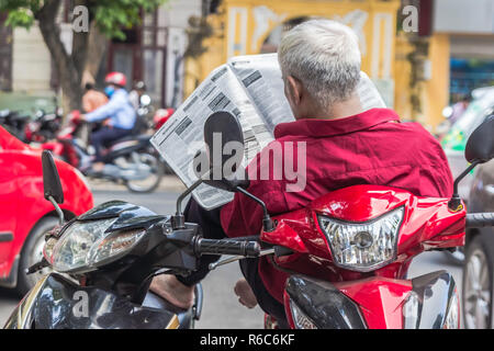 unrecognizable man in red shirt reads newspaper, sits on the scooter, traffic in the background, Hanoi Vietnam - Stock Image