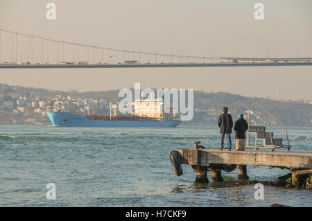 People watch a cargo ship sail under the Bosphorus bridge, from a pier on the Asian Side. - Stock Image