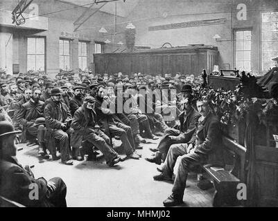 Men and boys seated on benches inside a charitable East End Mission       Date: 1895 - Stock Image