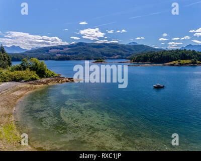 The Ambient Light tour boat near a beach inside the Broughton Archipelago Marine Park, First Nations Territory, British Columbia, Canada. - Stock Image