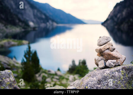 Close-up of stack of stones against lake - Stock Image