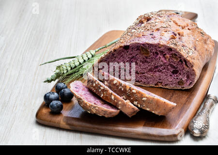 Blueberry  and chia seed bloomer on white wooden table - Stock Image