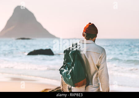 Man with backpack walking at ocean beach summer traveling journey vacations tourist fashion lifestyle adventure outdoor in Norway solitude emotions - Stock Image