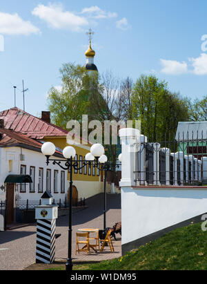 View of quiet old street of Russian city of Vladimir with golden dome of Saint George Church in blue sky on background - Stock Image