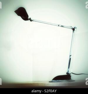 Monochrome, minimalistic photo of modern angle poise style office desk lamp on white background. - Stock Image