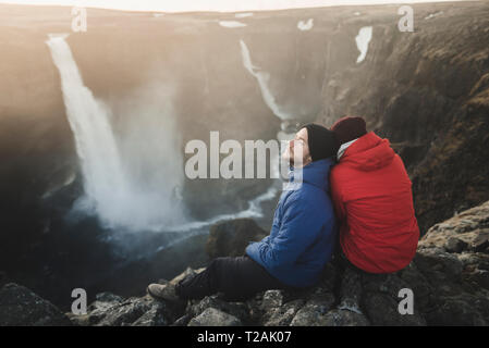 Hiker couple sitting on cliff by Haifoss waterfall in Iceland - Stock Image