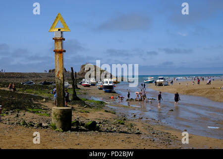 Bude, Cornwall, UK. Holidaymakers enjoy the beach at low tide at Breakwater Beach looking out into Sir Thomas's Pit and Summerleaze Beach - Stock Image