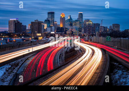 Light trails and the Minneapolis, Minnesota skyline at dusk as seen from the 24th Street walking bridge over Interstate 35W. - Stock Image