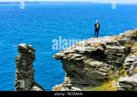 A man standing on a cliff edge, Tintagel Peninsula, Cornwall,England,UK - Stock Image