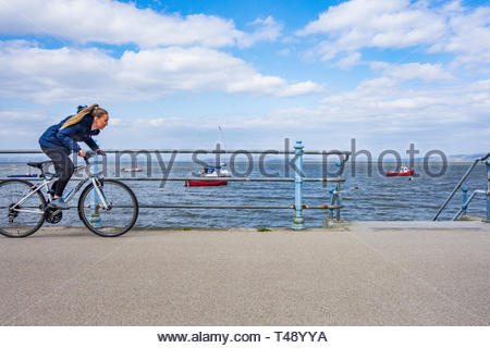 A cyclist pedaling hard along the Promenade at Morecambe, Lancashire, England UK with the boats floating on a high tide - Stock Image
