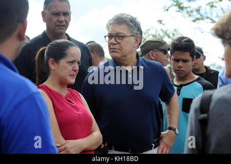 U.S. Minnesota Senator Al Franken (middle) meets with Puerto Rican residents at the site of a large landslide during - Stock Image