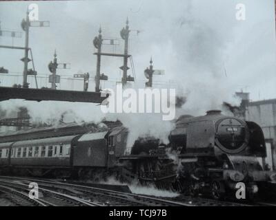 City of Manchester (Princess Coronoation Class) heads a train of LMS design coaches away from Shrewsbury. Steam train at Shrewsbury Railway Station in the 1950s. Shrewsbury, Shropshire, England, UK - Stock Image