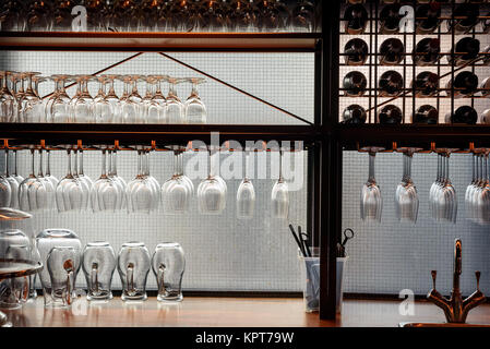 Rows of bar beer and wine glasses in a light display at night - Stock Image