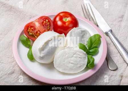 Fresh soft white mozzarella cheese from Italy seerved with fresh ripe tomatoes, basil and olive oil - Stock Image