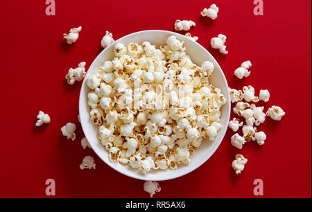 Popcorn in a white bowl. Directly above shot of popcorn against red background. - Stock Image