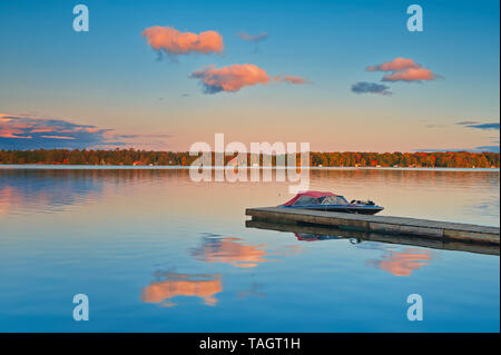 Dock and boats on Silent Lake at sunset Silent Lake Provincial Park Ontario Canada - Stock Image