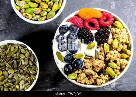Breakfast Bowl of Cereals Yogurt and Fruit With BLueberries, Blackberries, Apricot, Pistachio Nuts, Raspberries and Oat Clusters In A Bowl - Stock Image