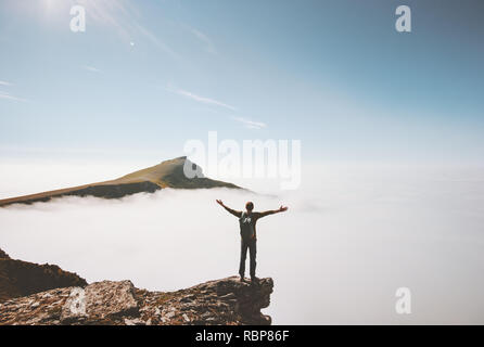 Happy man traveler standing alone on cliff edge mountain over clouds enjoying view active adventure travel lifestyle vacations outdoor success emotion - Stock Image