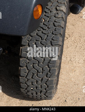 An aggressive off-road tire mounted on a Jeep sitting in the sand. - Stock Image