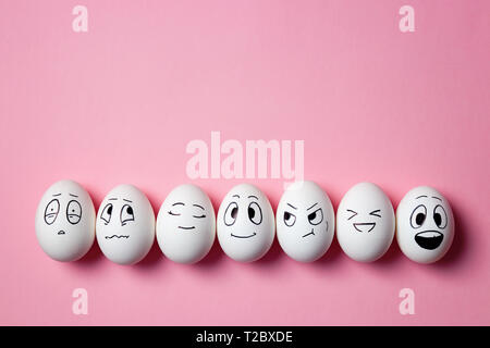 Funny Easter eggs with facial expressions. Eggs with different faces on pink background. - Stock Image