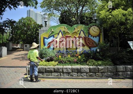 Man watering garden bed at entrance to Kowloon Park. Tsim Sha Tsui, Kowloon, Hong Kong, China - Stock Image