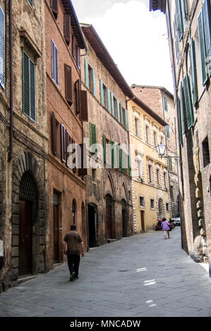 one man walks down a deserted street in Siena Italy flanked by 14th or 15th century construction and paving stones underfoot - Stock Image