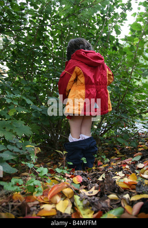 Boy urinating in the bushes - Stock Image