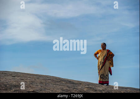 A lady on her own, wearing a sari, looks majestic, standing at the top of a mountain near Chennai, India - Stock Image