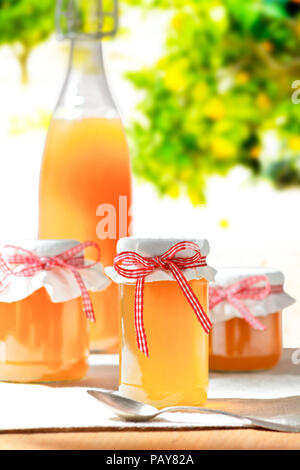 Homemade fruit juice in a glass bottle and jelly in jars with linen cover and a nostalgic ribbon bow in bright sunshine, fruit trees in the background - Stock Image