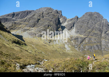 Two hill walkers below Bla Bheinn (centre) and Clach Glas (right) in the Black Cuillin Mountains on the Isle of Skye, Scotland, UK - Stock Image