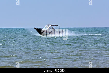 Crestliner Super Hawk sport fishing and ski boat traveling at high speed on Lake Michigan - Stock Image