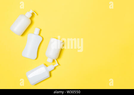 Set of White Cosmetic containers isolated on yellow background, top view with copy space. Group of plastic bodycare bottle containers with empty space - Stock Image