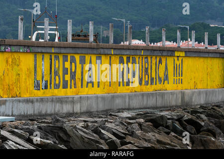 Freedom and Republic.  Political stencil message created with yellow paint over a graffiti covered wall  looking over the  Mediterranean Sea. - Stock Image