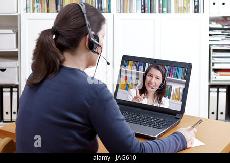 Woman with pen and paper and a headset in front of her laptop making a video call with her friendly tutor, text - Stock Image