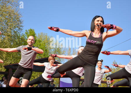 Nis, Serbia - April 20, 2019 Young group of people participating in the free public Piloxing class in summer at park - Stock Image