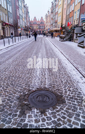 Municipal drain cover anv view of cobbled street and the Great Armoury, 1609, now Academy of Fine Arts, Ulica Piwna, Gdańsk, Poland - Stock Image