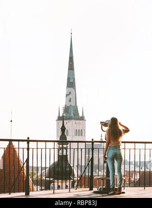 Woman sightseeing in Tallinn city Europe vacations in Estonia travel lifestyle girl tourist at viewpoint St Olav's Church Old Town architecture - Stock Image
