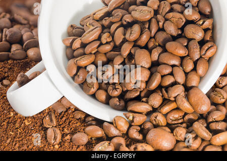 Picture of a white cup filled with coffee beans - Stock Image