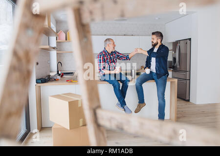 A mature man with his senior father furnishing new house, a new home concept. - Stock Image