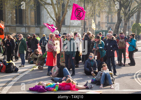 Demonstrators sit in the road blocking Victoria Street by Parliament Square, Westminster for the Extinction Rebellion demonstration - Stock Image