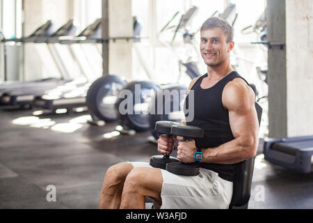 Side view portrait of young adult man muscular built handsome athlete working out in a gym, sitting on a weightlifting machine and holding two dumbbel - Stock Image