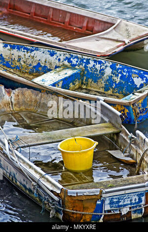 A collection of small and neglected rowing boats, all of which have seen better days! - Stock Image