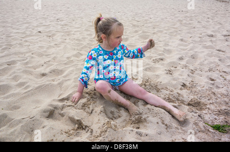3 year old girl playing in sand at the beach. - Stock Image