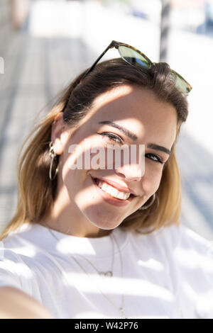 Beautiful smiling girl wearing casual summer clothes enjoys sunny day. Beauty, fashion shot. - Stock Image