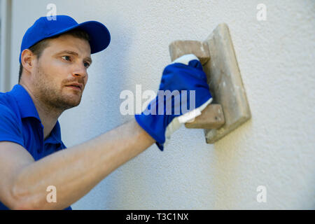 worker applying decorative facade plaster on house wall - Stock Image